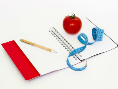 tomato-measuring-tape-and-ballpen-on-notebook